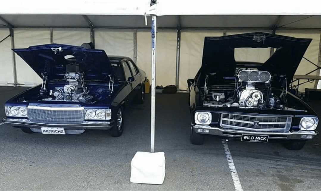 2 cars inside a marquee